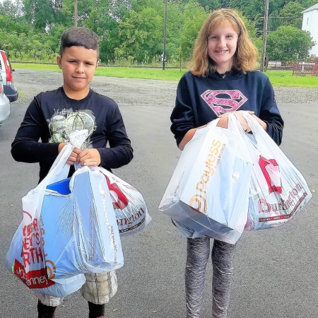 2 children with bags of donated items